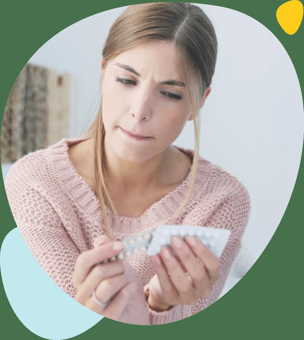 Une jeune fille dubitative regarde une plaquette de pilule