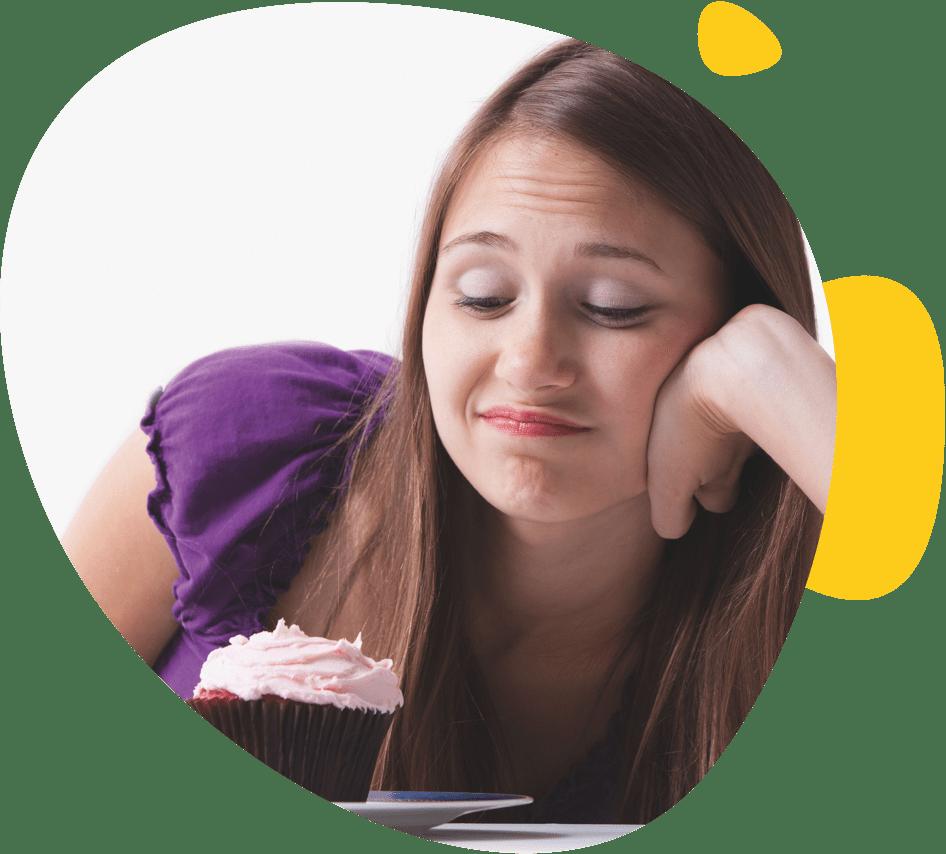 Une adolescente regarde avec envie un muffin