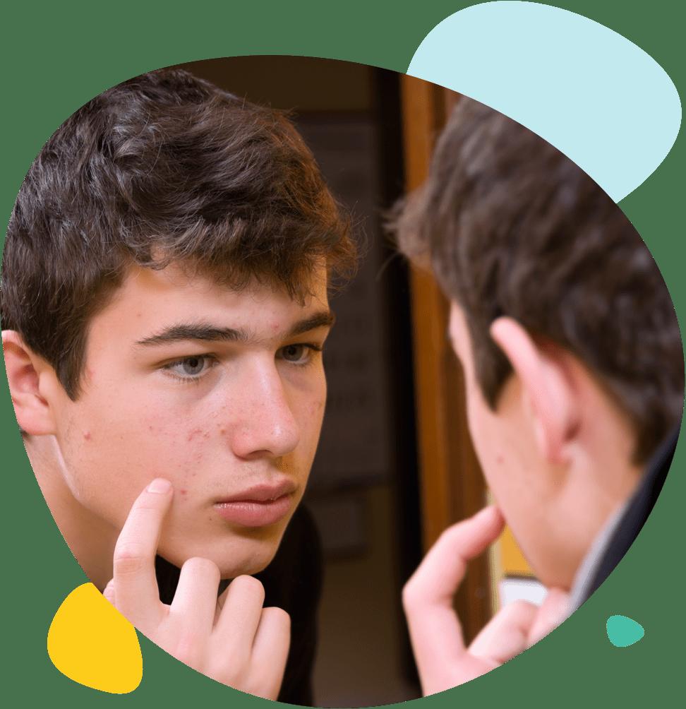 Un jeune homme regarde ses boutons dans le miroir