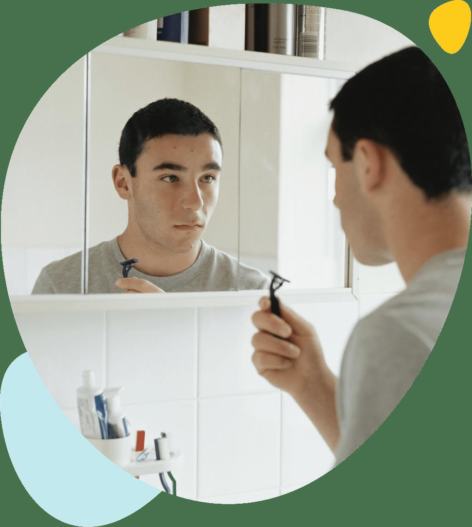 Un jeune homme avec des boutons est en train de se raser