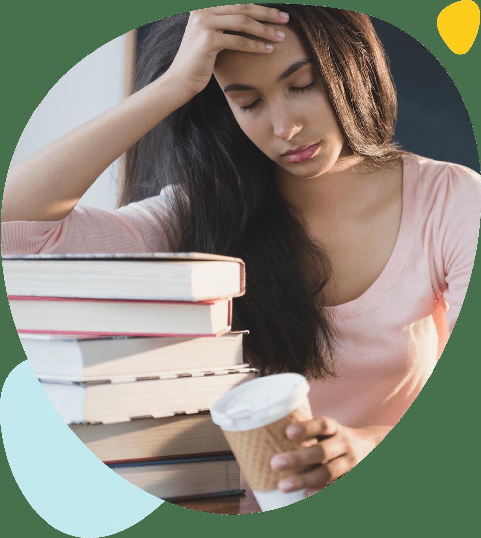 Une jeune fille épuisée s'accoude sur ses livres avec un café dans la main