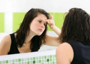 Une jeune fille se regarde dans un miroir